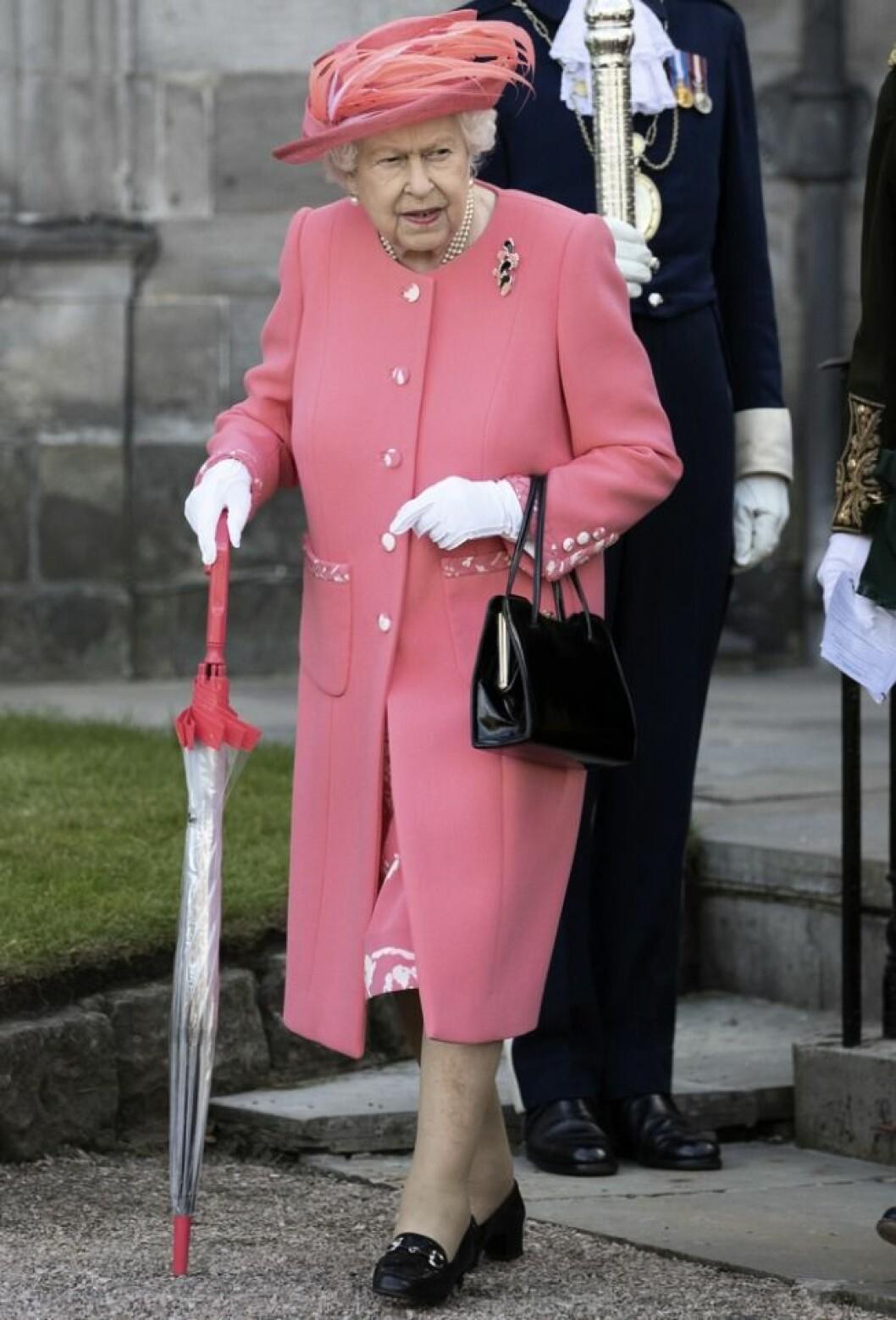 Drottning Elizabeth går med paraply som käpp