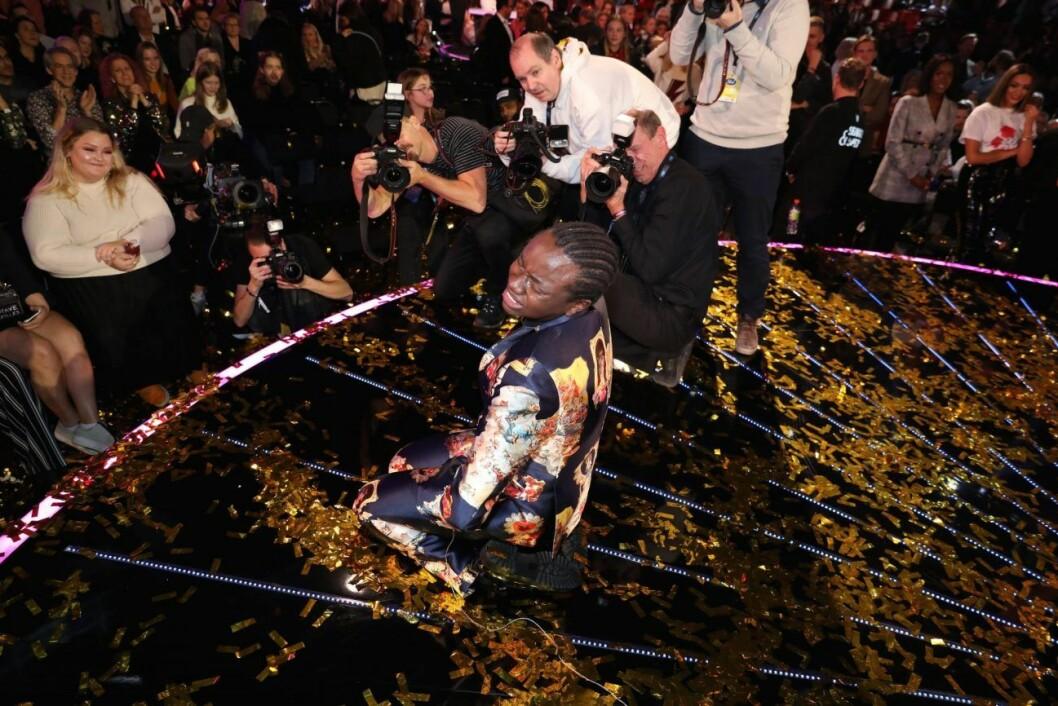 Tusse Chiza sitter på en scen med glitter och gråter av glädje.