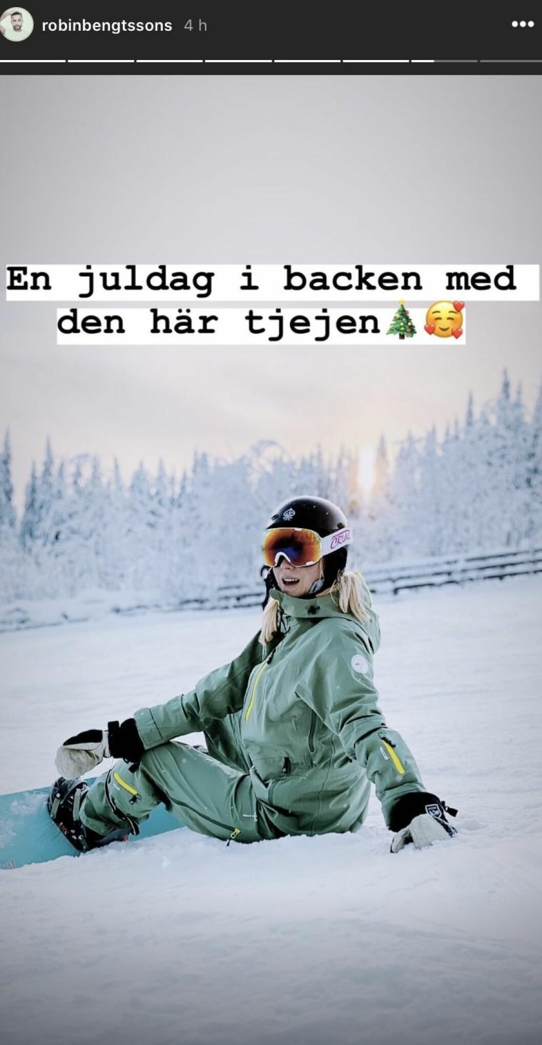 Sigrid bernson sitter i snö med en snowboard